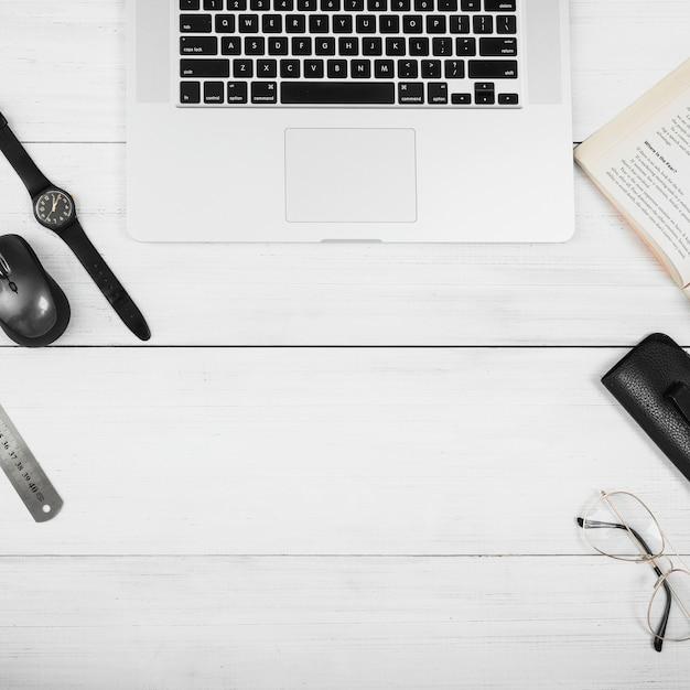 Un tavolo in legno bianco con computer portatile; topo; occhiali; libro e orologio da polso sulla scrivania bianca Foto Gratuite