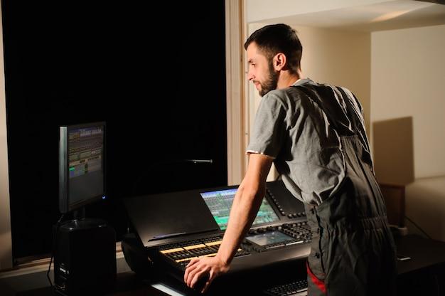 Un tecnico dell'illuminazione lavora con il controllo dei tecnici delle luci durante lo spettacolo. mixer professionale, consolle di missaggio. attrezzature per concerti Foto Premium