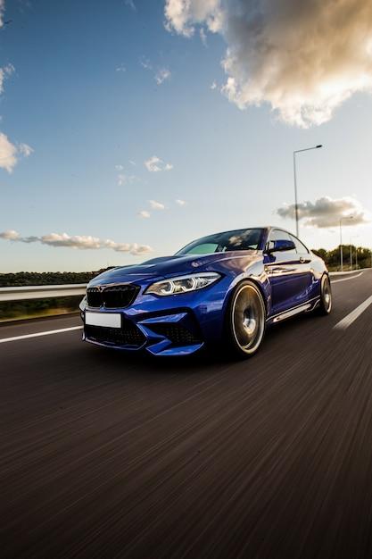 Un test drive berlina sportiva blu su strada. Foto Gratuite