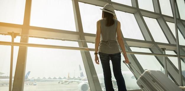 Un turista femmina cammina su una sedia a rotelle in un aeroporto per viaggiare in aereo. concetto di viaggio Foto Premium
