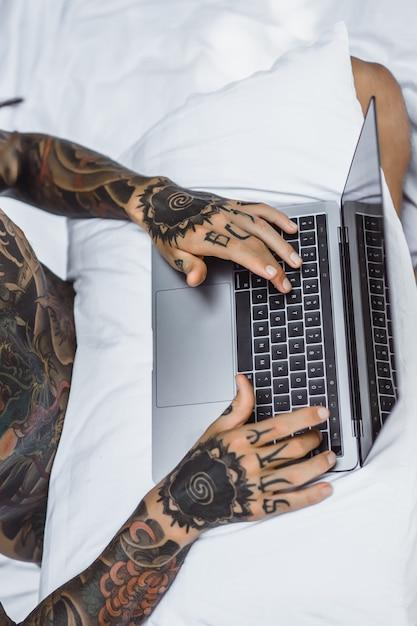Un uomo a letto che lavora a un laptop, controlla la posta, guarda un film, ascolta la musica Foto Gratuite