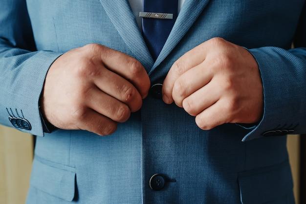 Un uomo abbottonarsi una giacca blu Foto Premium