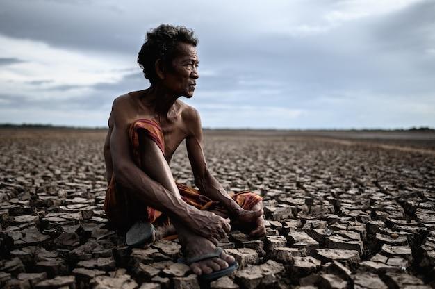 Un uomo anziano seduto abbracciando le ginocchia si chinò su un terreno asciutto e guardò il cielo Foto Gratuite