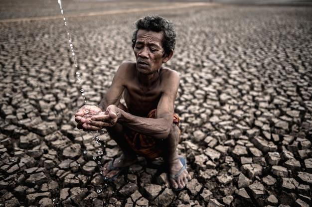 Un uomo anziano seduto in contatto con la pioggia nella stagione secca, riscaldamento globale, messa a fuoco selettiva Foto Gratuite