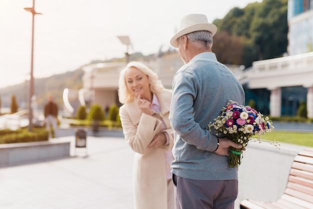 Un uomo anziano tiene in mano un mazzo di fiori dietro la schiena. Foto Premium