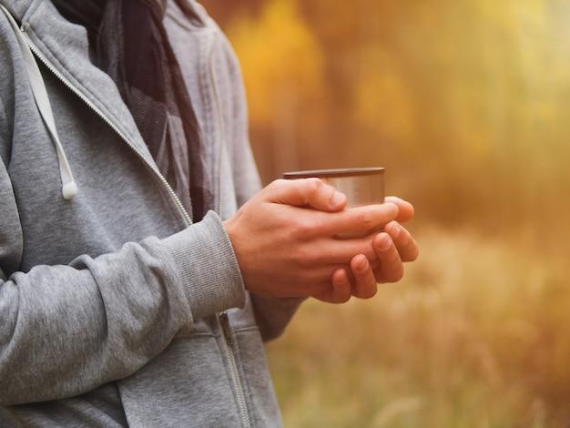Un uomo beve il tè caldo da un thermos in natura in autunno Foto Premium