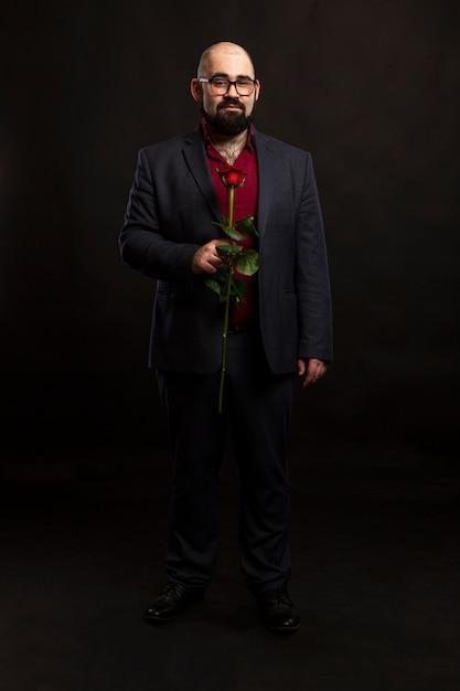 Un uomo calvo con gli occhiali e con la barba in abito con una rosa rossa in mano. Foto Premium
