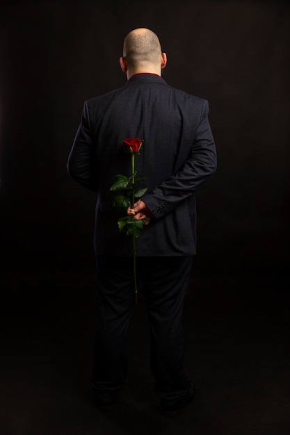 Un uomo calvo in giacca e cravatta tiene una rosa rossa dietro la schiena. a tutta altezza. Foto Premium