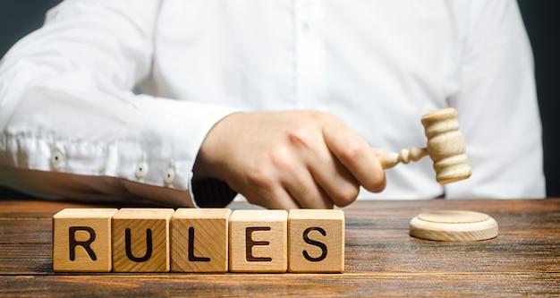 Un uomo che batte un martello pubblica nuove regole e leggi. impostazione di regole e restrizioni chiare. Foto Premium