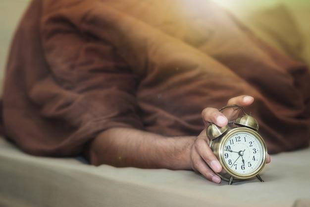 Un uomo che giace sotto una coperta marrone sta uscendo dalla sveglia con sonnolenza. Foto Premium