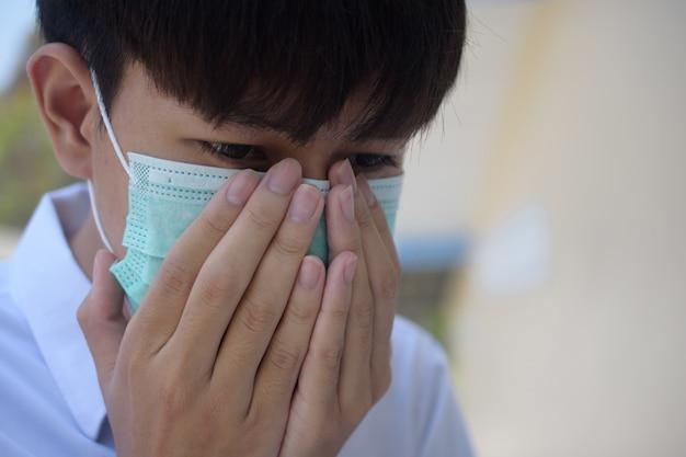 Un uomo che indossa una maschera chirurgica per coprirsi il naso con tosse e starnuti a causa di malattie al fine di prevenire la diffusione di virus e germi ad altri, la maschera per il viso protegge il virus corona 2019 Foto Premium