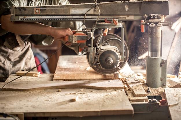 Un uomo che lavora con prodotti in legno sulla macchina Foto Gratuite