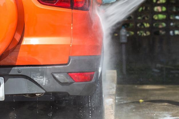Un uomo che spruzza l'idropulitrice per l'autolavaggio nel negozio di cura dell'auto Foto Premium