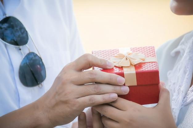 Un uomo che tiene una confezione regalo per la fidanzata sorpresa. Foto Premium