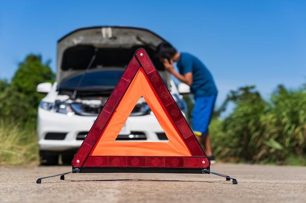 Un uomo che utilizza un telefono mentre ha un problema auto e un segnale di avvertimento triangolo rosso sulla strada Foto Premium