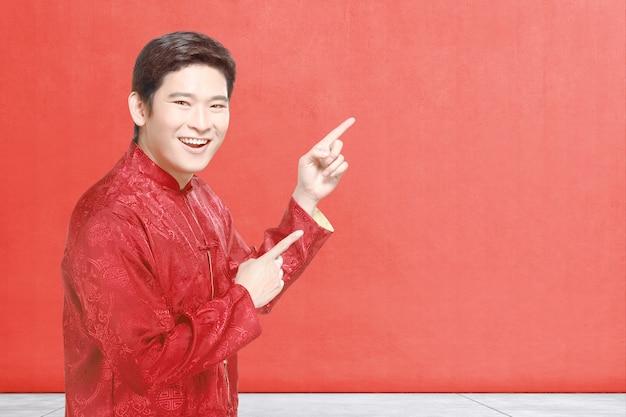 Un uomo cinese asiatico in abito cheongsam celebra il capodanno cinese Foto Premium