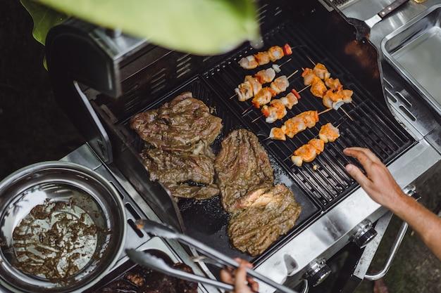 Un uomo con tatuaggi fa carne alla griglia all'aperto. Foto Gratuite