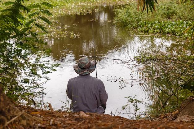 Un uomo con un cappello lancia una canna da pesca su un piccolo stagno Foto Premium