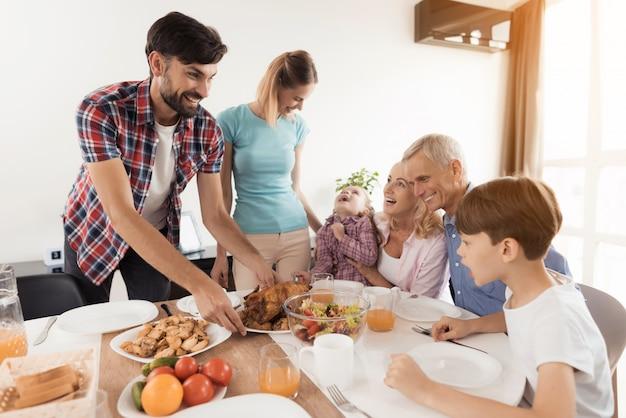 Un uomo con una donna serve una cena festiva sul tavolo Foto Premium