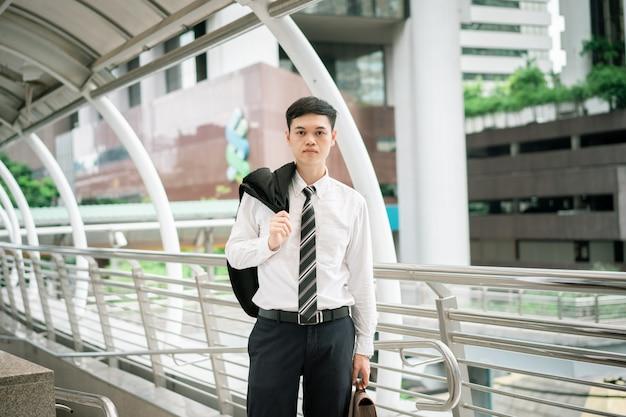 Un uomo d'affari indossa un abito nero, camicia bianca e cravatta. Foto Premium