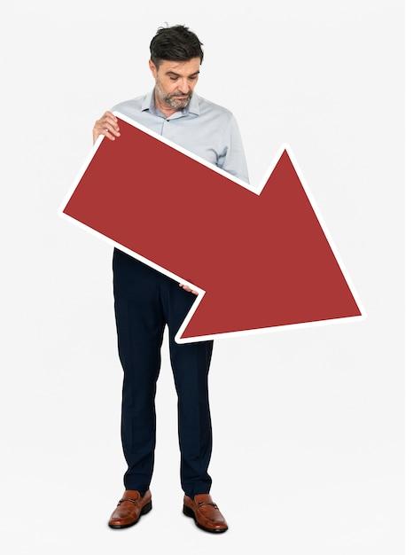 Un uomo d'affari infelice che tiene una freccia rossa Foto Gratuite
