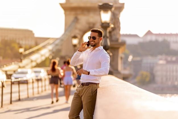 Un uomo d'affari su un ponte e parlando sul suo telefono Foto Premium
