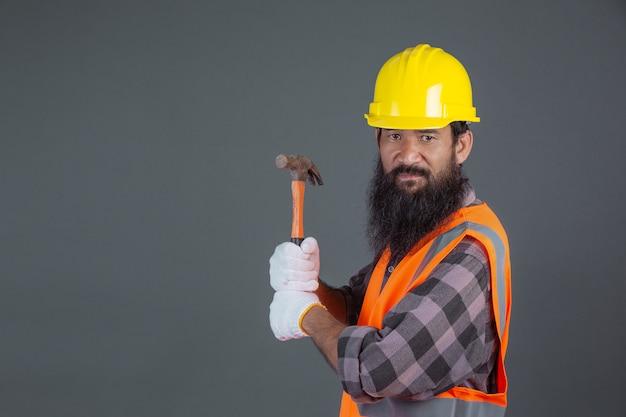 Un uomo di ingegneria che indossa un casco giallo con attrezzatura per l'edilizia su un grigio. Foto Gratuite