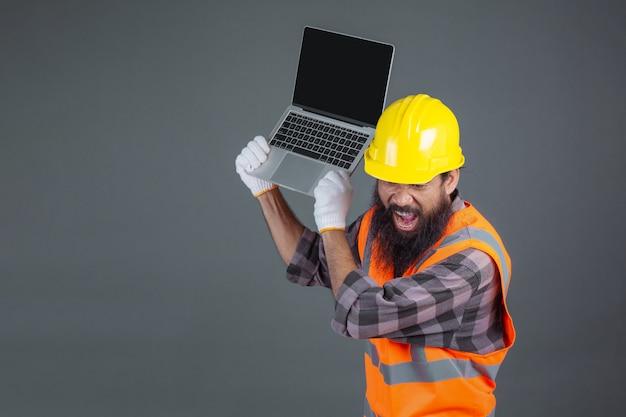 Un uomo di ingegneria che indossa un casco giallo in possesso di un notebook su un grigio. Foto Gratuite