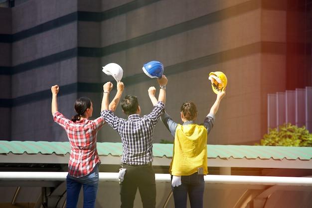 Un uomo e due donne lavoratrici stanno lavorando insieme al cantiere Foto Premium