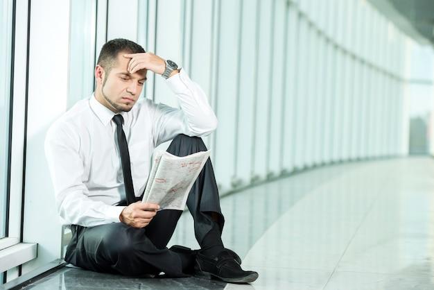 Un uomo è seduto con un giornale. Foto Premium