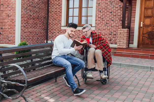 Un uomo e suo padre vicino alla casa di cura stanno leggendo un libro Foto Premium