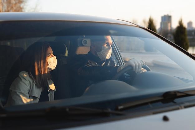 Un uomo e una donna che indossano maschere mediche e guanti di gomma per proteggersi da batteri e virus durante la guida di un'auto. uomini mascherati in macchina. coronavirus (covid-19 Foto Premium