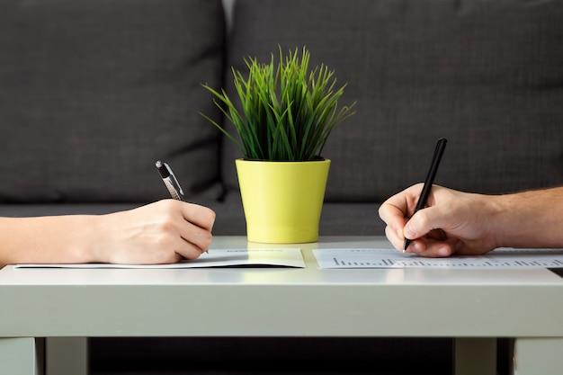 Un uomo e una donna firmano un accordo di divorzio, primo piano. litigio familiare, resa dei conti, divisione della proprietà, accordo di divorzio Foto Premium