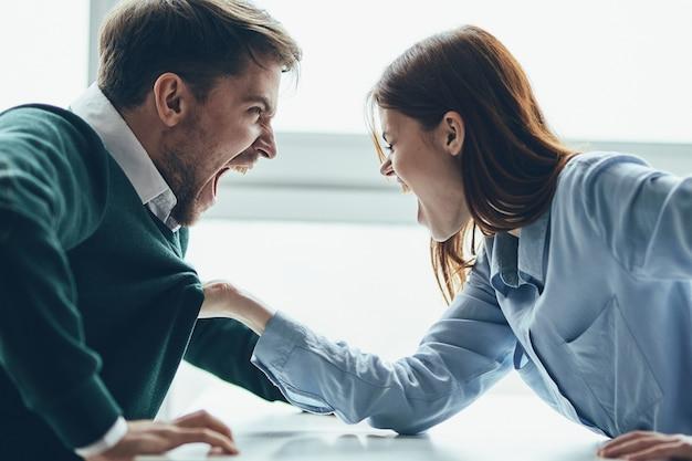 Un uomo e una donna sono seduti a un tavolo a discutere, litigare tra loro, un vero litigio, questioni familiari Foto Premium