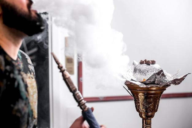 Un uomo fuma shisha con un'arancia e fuma intorno Foto Gratuite