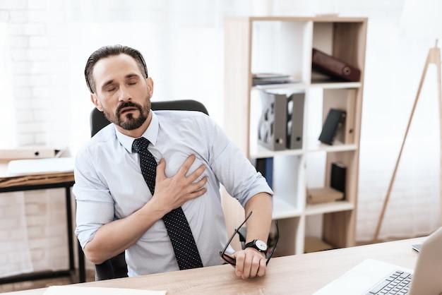Un uomo ha un cuore cattivo. tiene le mani sul petto. Foto Premium