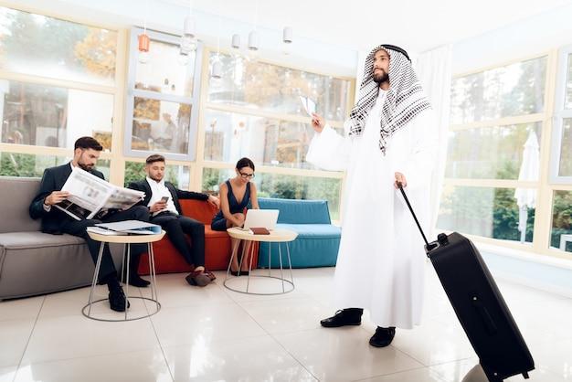 Un uomo in abiti arabi tiene in mano una valigia. Foto Premium