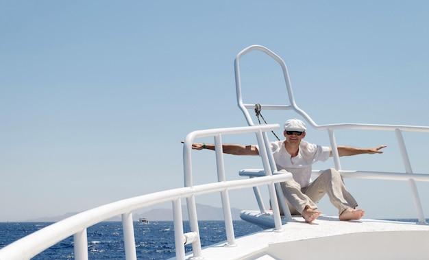 Un uomo in abiti luminosi che indossa un cappello e occhiali su uno yacht è felice di andarsene Foto Premium