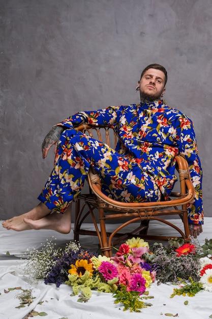 Un uomo in abito floreale seduta sulla sedia con fiori diversi sul pavimento Foto Gratuite