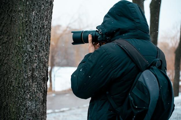 Un uomo in giacca con cappuccio e valigetta sulla schiena, con in mano una macchina fotografica e scattare foto Foto Premium