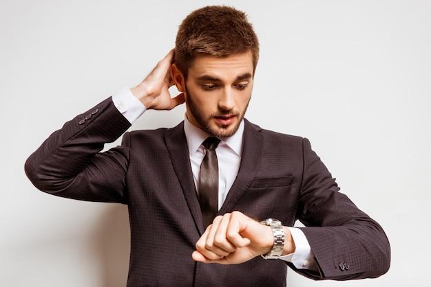 Un uomo in giacca e cravatta guarda l'orologio. Foto Premium