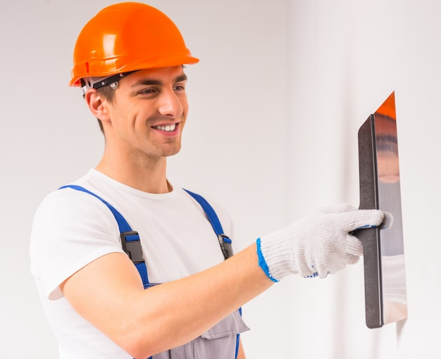 Un uomo in un pittore di elmetti dipinge un muro e sorride. Foto Premium
