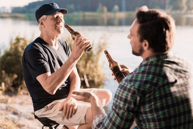 Un uomo in una camicia blu sta bevendo birra sul fiume Foto Premium
