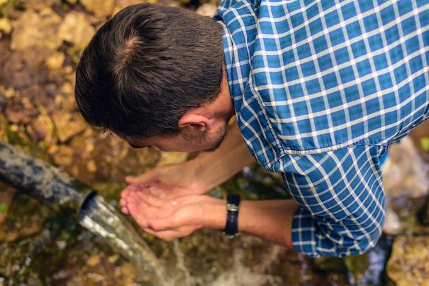 Un uomo in una camicia in una gabbia raccoglie acqua fresca da una sorgente a mani giunte, beve acqua da una fonte Foto Premium
