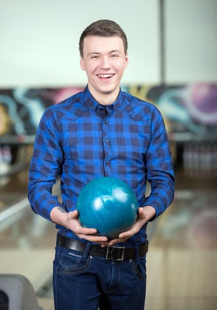 Un uomo in una camicia tiene una palla da bowling. Foto Premium