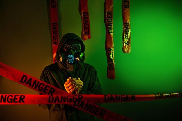 Un uomo in una tuta protettiva verde scuro con una maschera antigas sul viso e un cappuccio in testa in posa in piedi vicino a una parete verde con nastri di pericolo appesi. concetto di pericolo Foto Premium