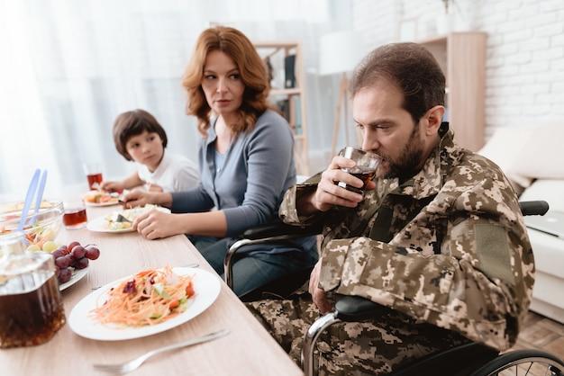 Un uomo in uniforme è seduto al tavolo della cucina. Foto Premium