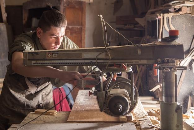 Un uomo lavora sulla macchina con il prodotto in legno Foto Gratuite