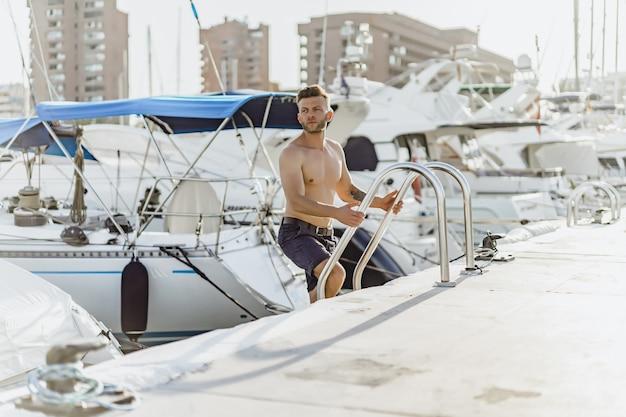 Un uomo nel porto che prepara lo yacht per il viaggio Foto Gratuite