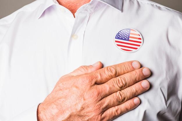 Un uomo patriottico con il distintivo degli sua sulla sua camicia bianca che tocca la mano sul suo petto Foto Gratuite